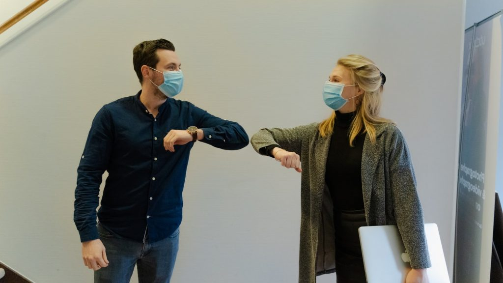 male and female colleagues with surgeon masks touching elbows