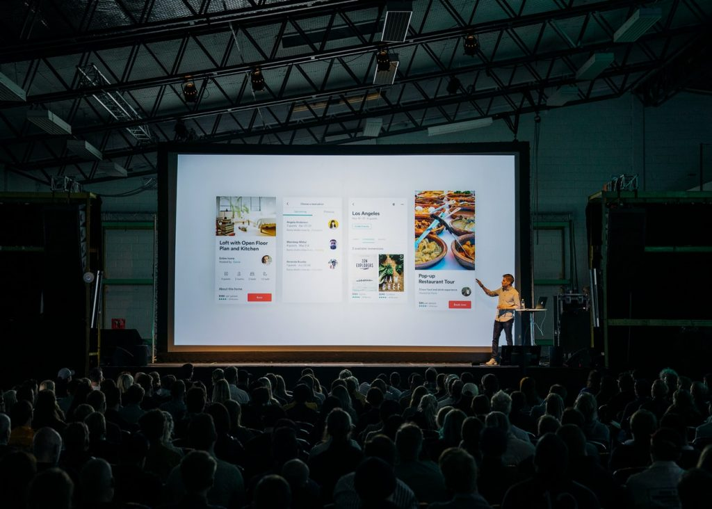 man doing a presentation in front of a crowd in a hangar-like building